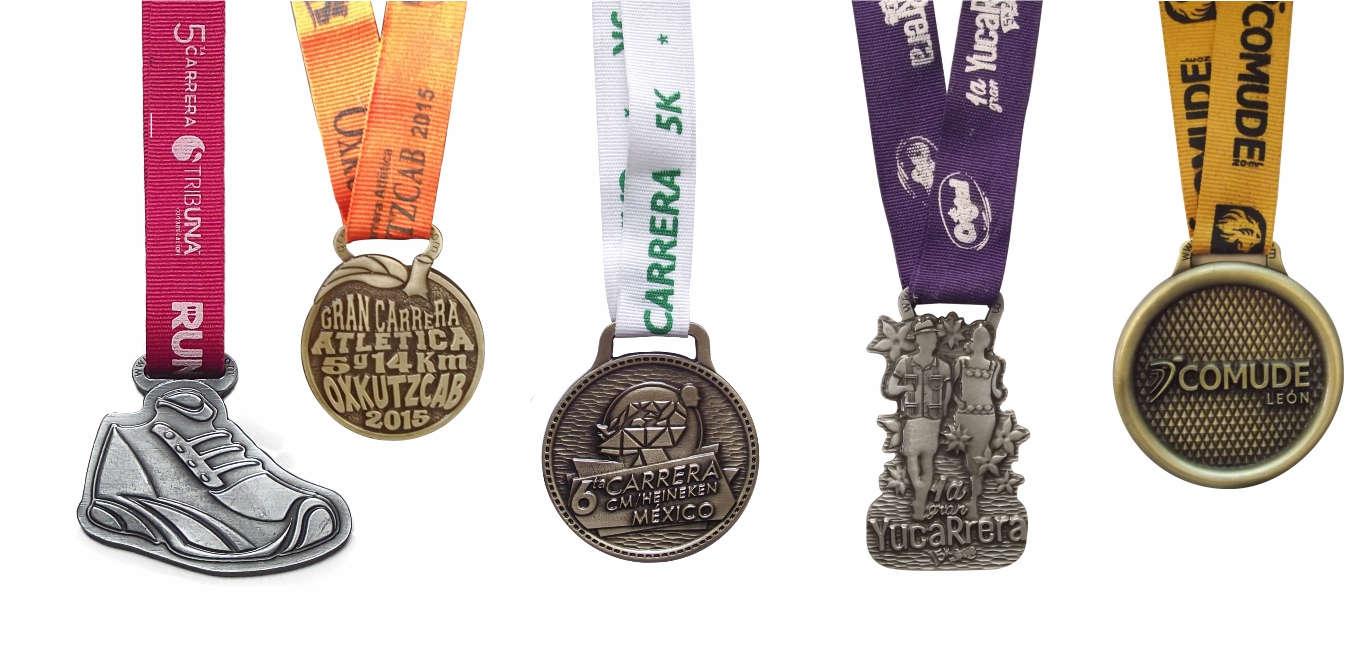 Imagen con varias medallas con listones con serigrafía a una tinta. Primera medalla con forma de zapato, listón rojo y serigrafía blanca, tercera medalla con forma de corredores, liston morado y serigrafía blanca