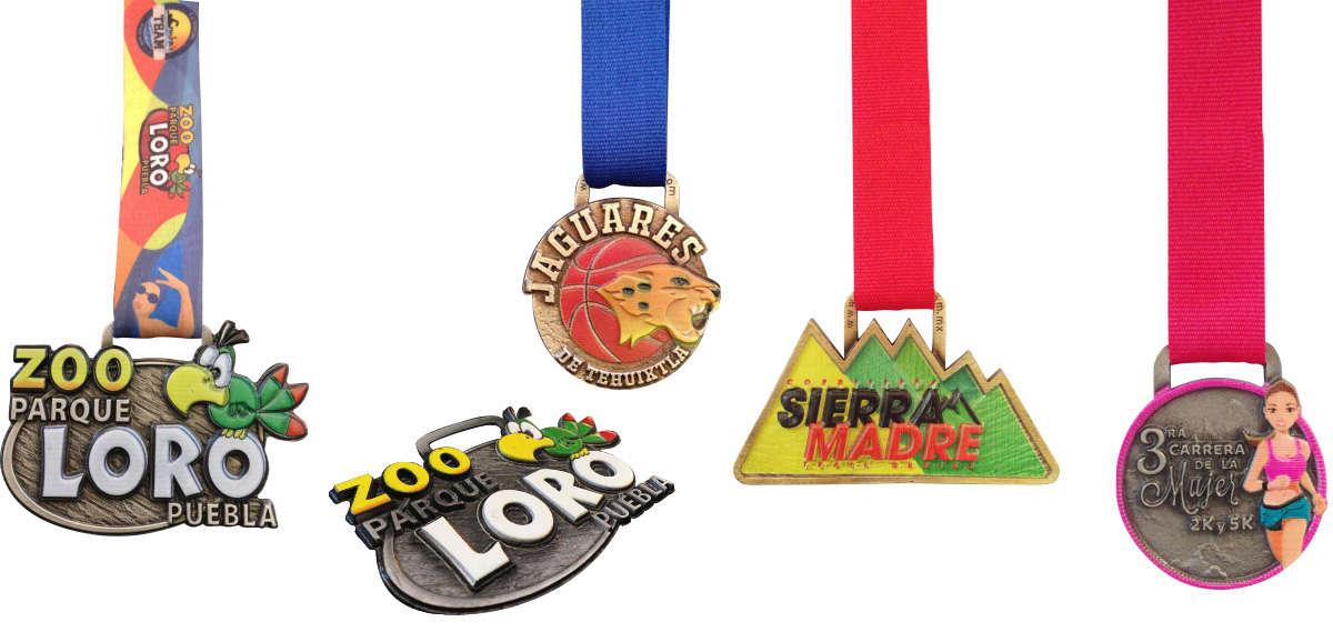 imagen de varias medallas con superficies impresas con UV. La primera medalla con forma del Zoo Parque Loro Puebla con impresión en diversos colores. La cuarta medalla con forma redonda y forma una mujer corriendo en la 3ra carrera de la mujer