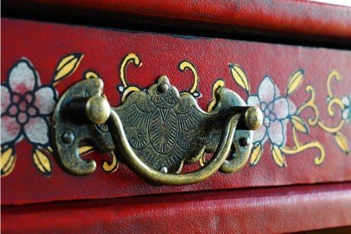 imagen de un mueble rojo con un herraje en latón