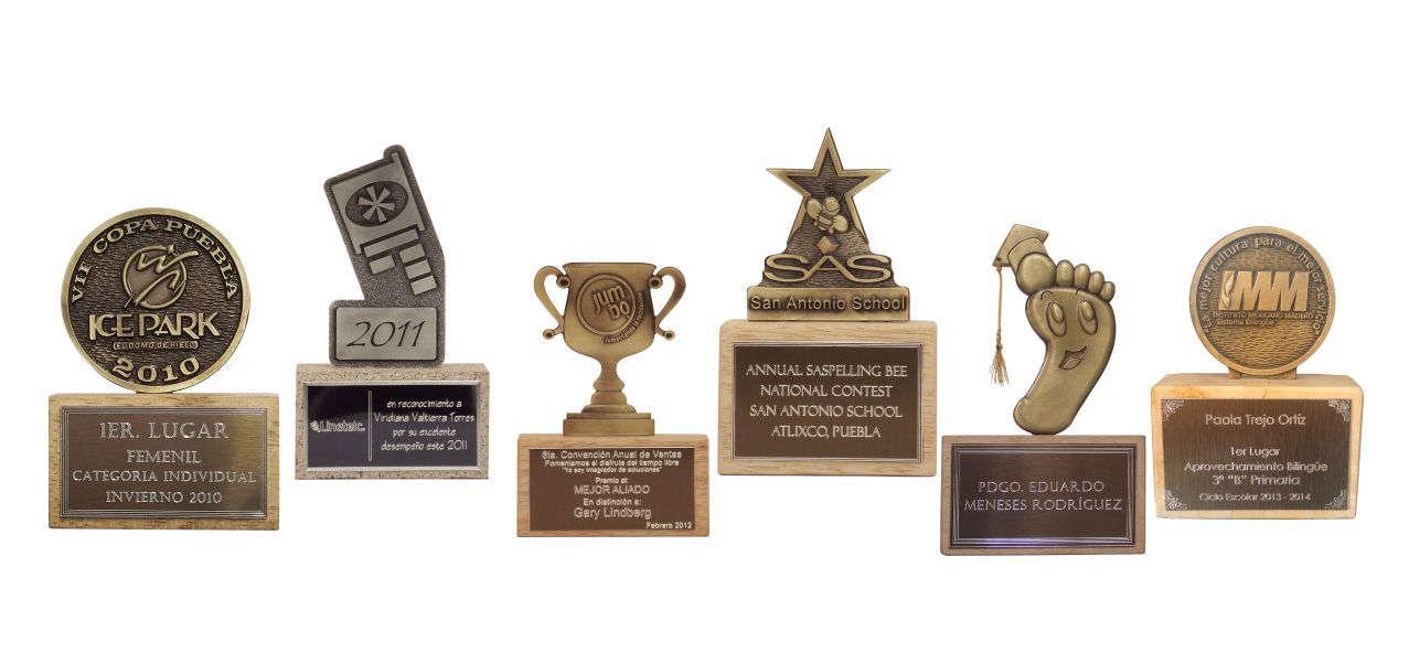 imagen de varios mini trofeos personalizados con diferentes formas, con placas grabadas en diamante y bases de madera para empresas y eventos deportivos