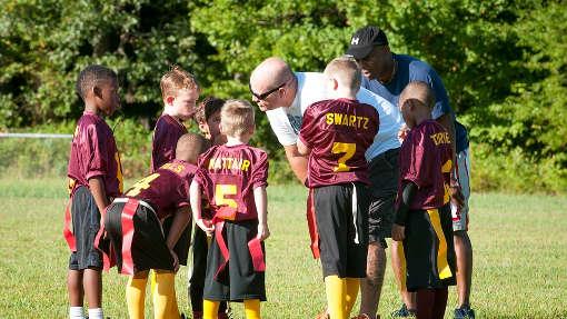 imagen de un entrenador de futbol, aconsejando y entrenando a sus niños